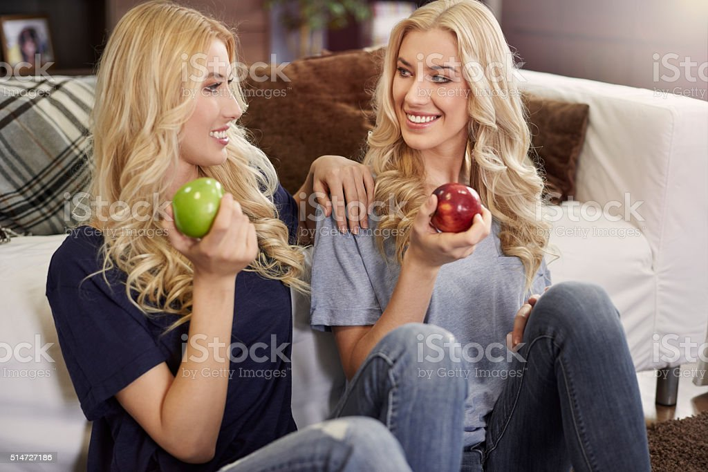 Blonde twins eating fresh apples stock photo