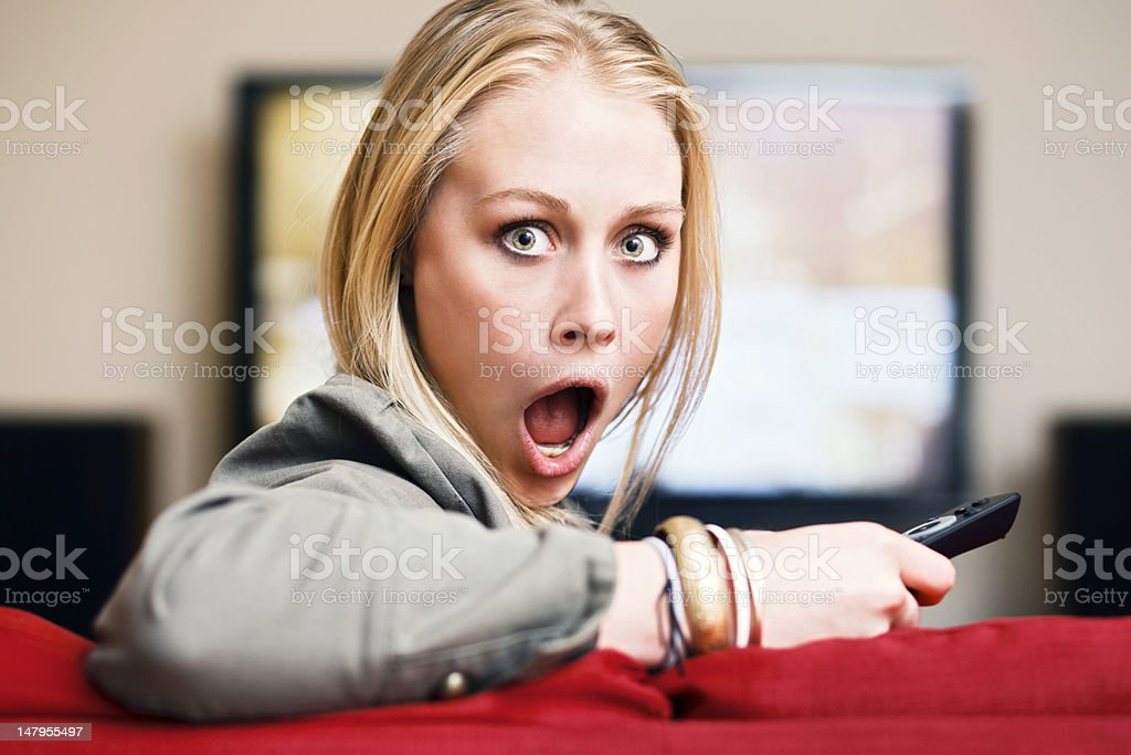 Blonde watching TV and holding remote control looks round, horrified royalty-free stock photo