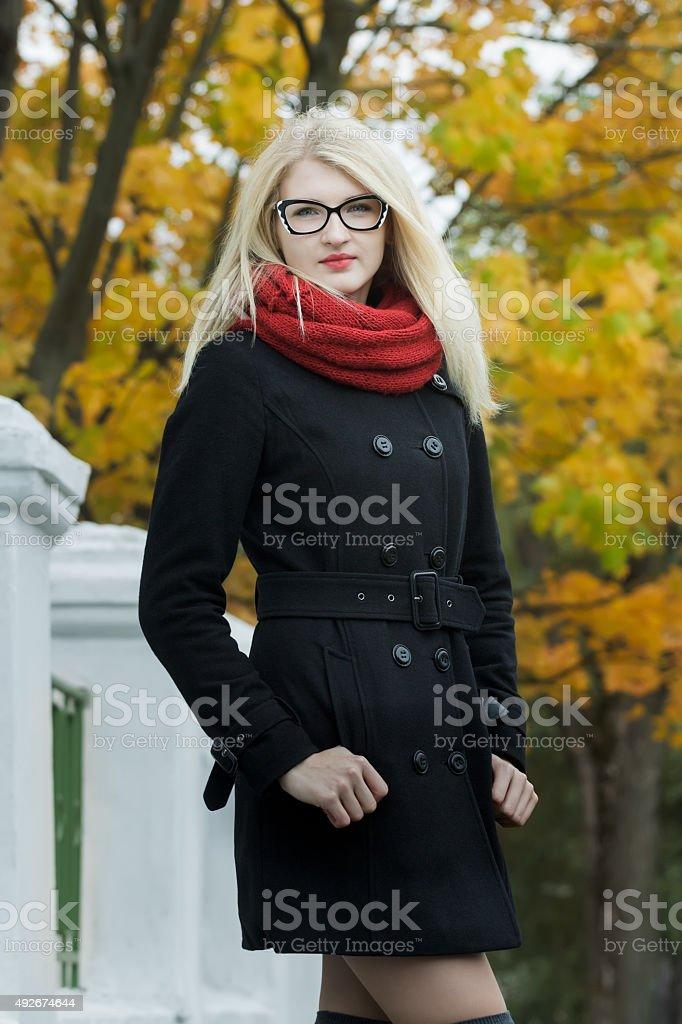 Blonde wearing cat eye glasses posing on street stock photo