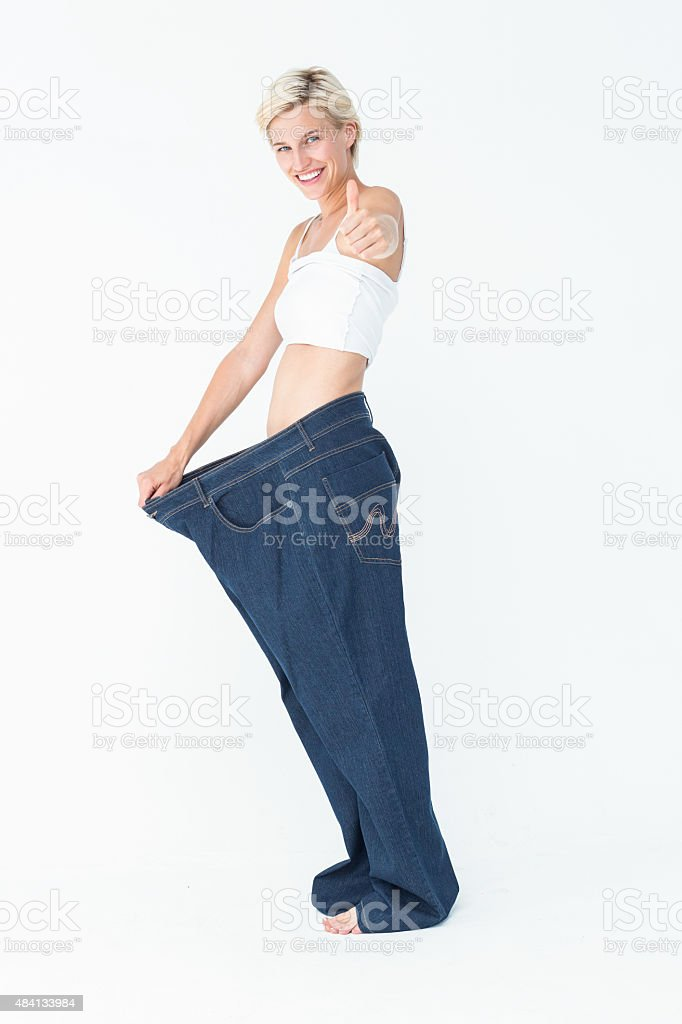Blonde wearing too large pants with the thumb up stock photo