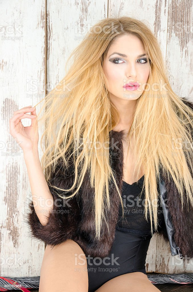 Blonde with a black coat and long blond hair stock photo