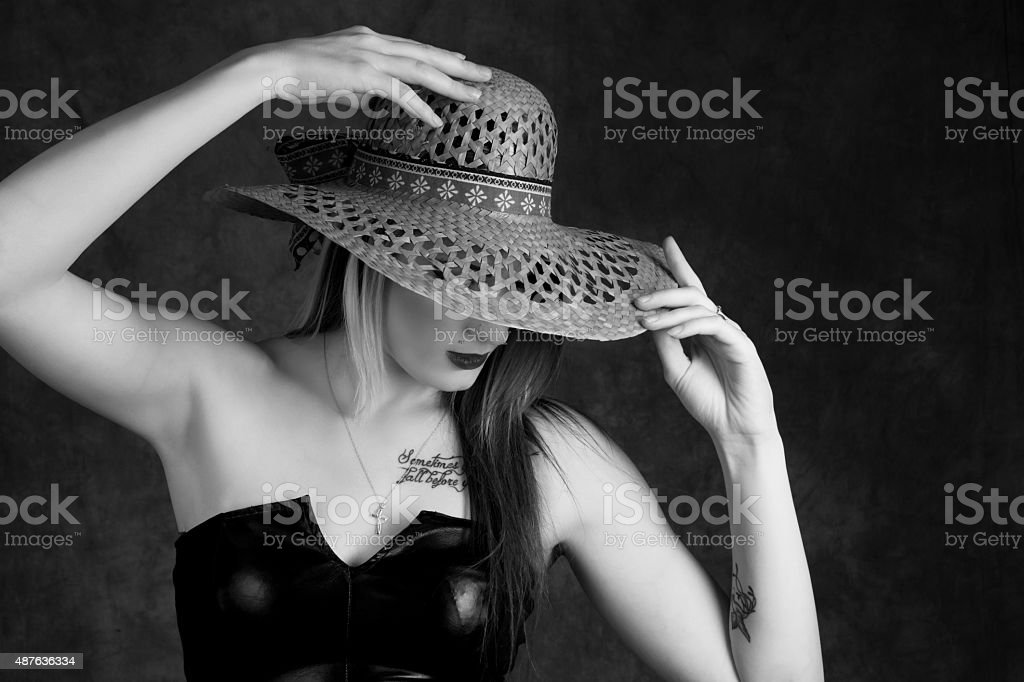 B&W blonde with both hands on sun hat, waist up. stock photo