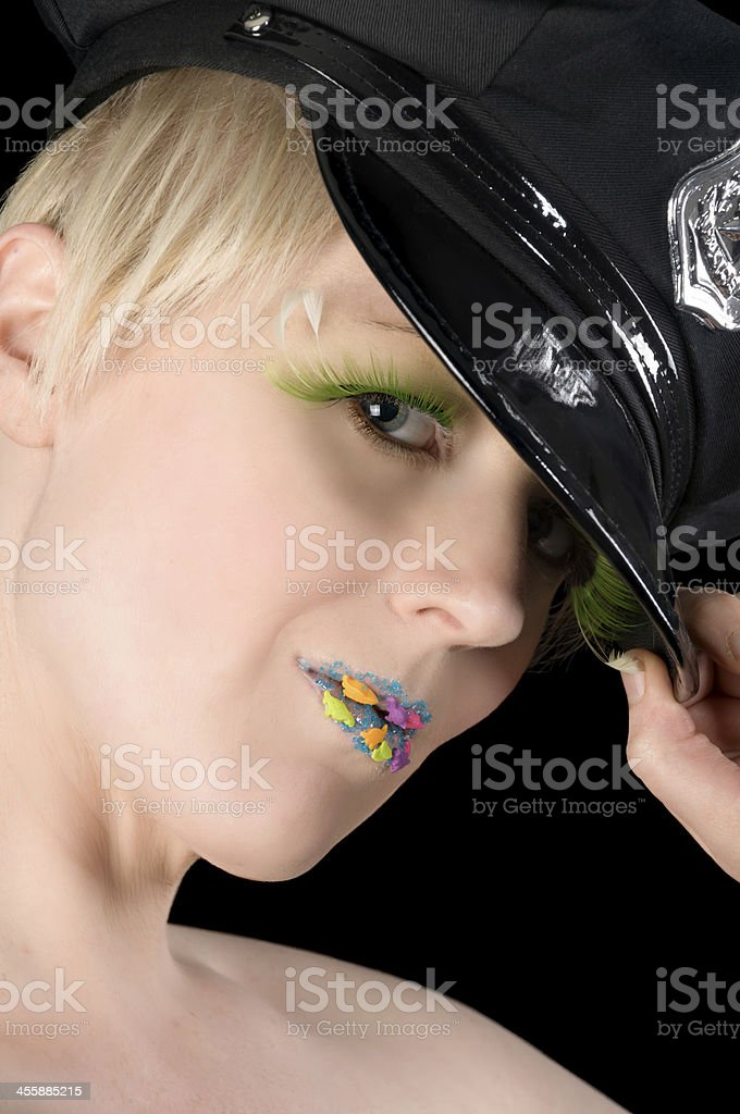 Blonde with candy lips tipping cop hat. stock photo
