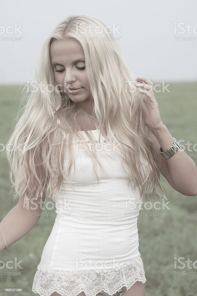Blonde with downcast eyes is on the field stock photo