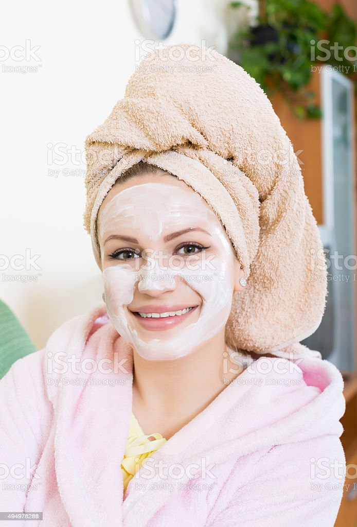 blonde with face pack relaxing on sofa indoors stock photo