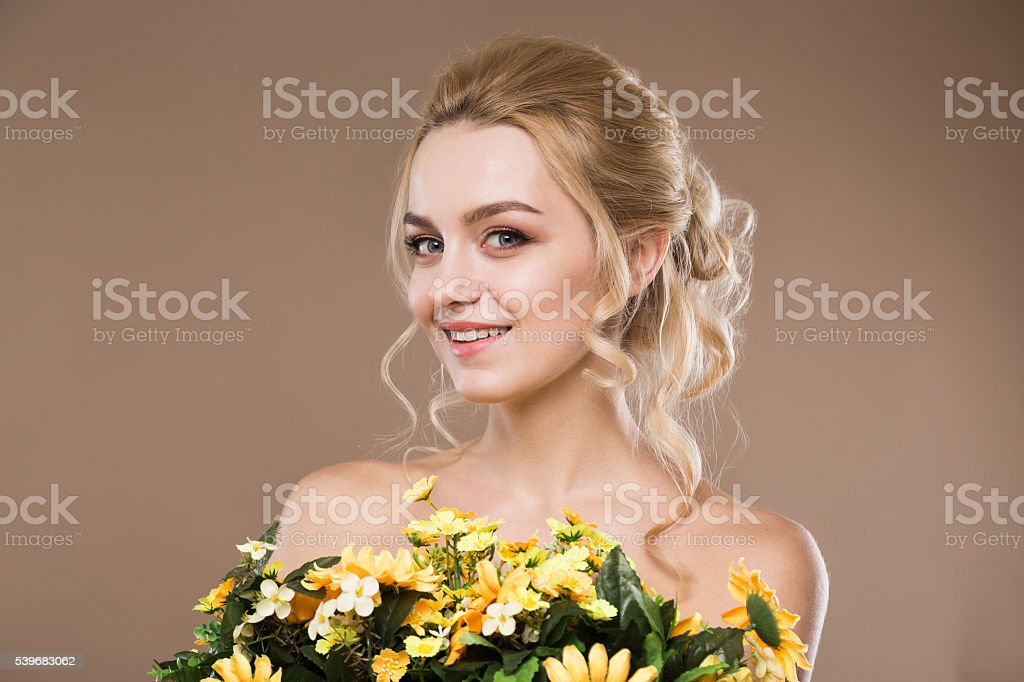 blonde with flowers in their hands stock photo