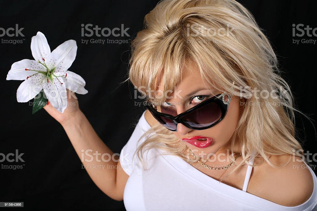 blonde with glasses and madonna lily stock photo