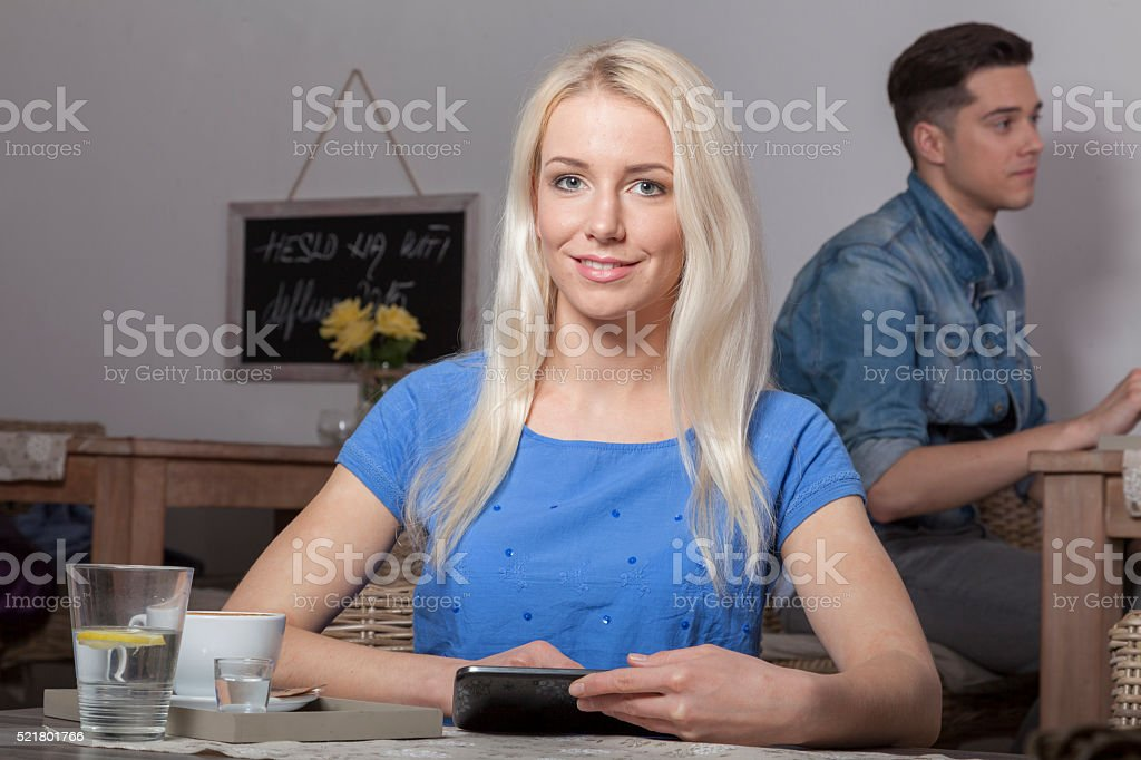 Blonde with tablet sitting in cafeteria environment stock photo