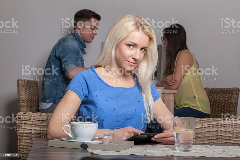 Blonde with tablet sitting in cafeteria stock photo