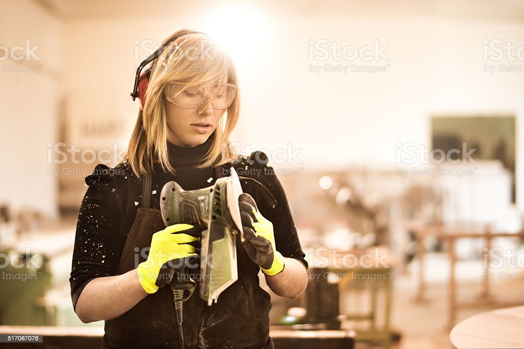 Blonde woman and power sander stock photo