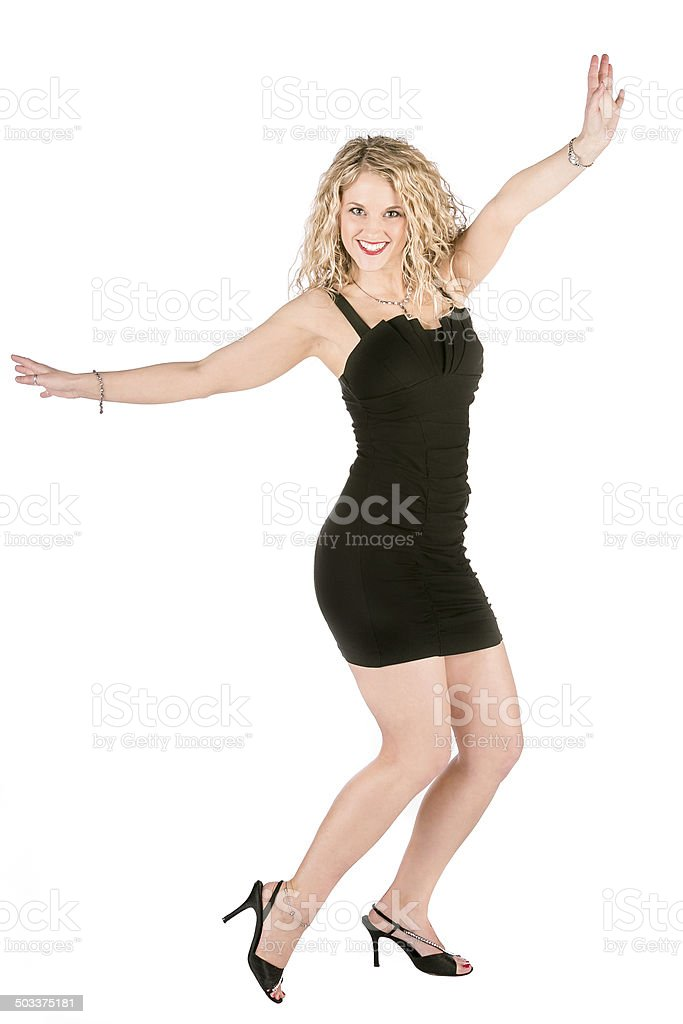 blonde woman black dress, arms up, smiling, high heels stock photo