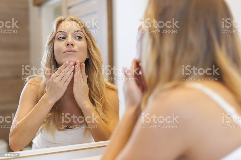 Blonde woman caring about her skin on face stock photo