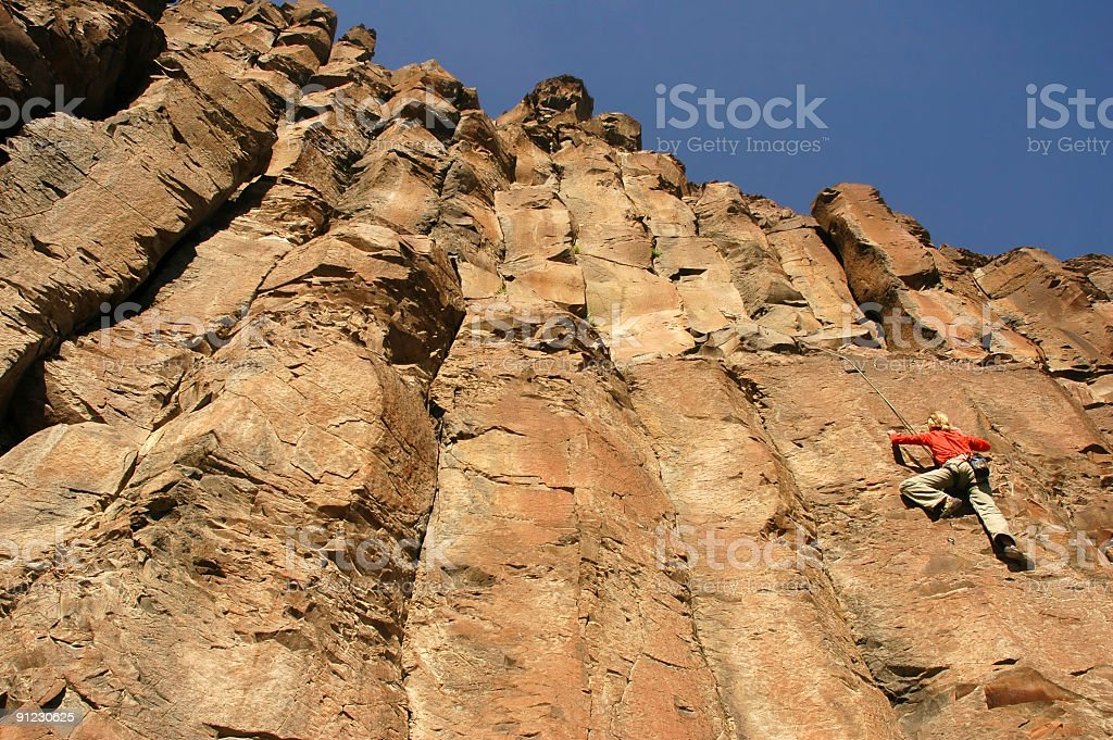 Blonde woman climbing to the top of a steep cliff royalty-free stock photo