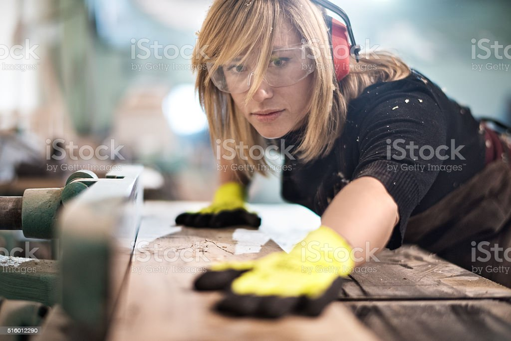 Blonde woman cutting a plank stock photo