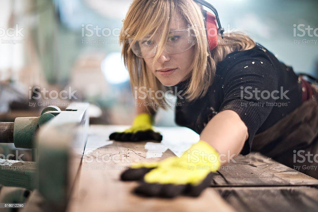 Blonde woman cutting a plank stock photo