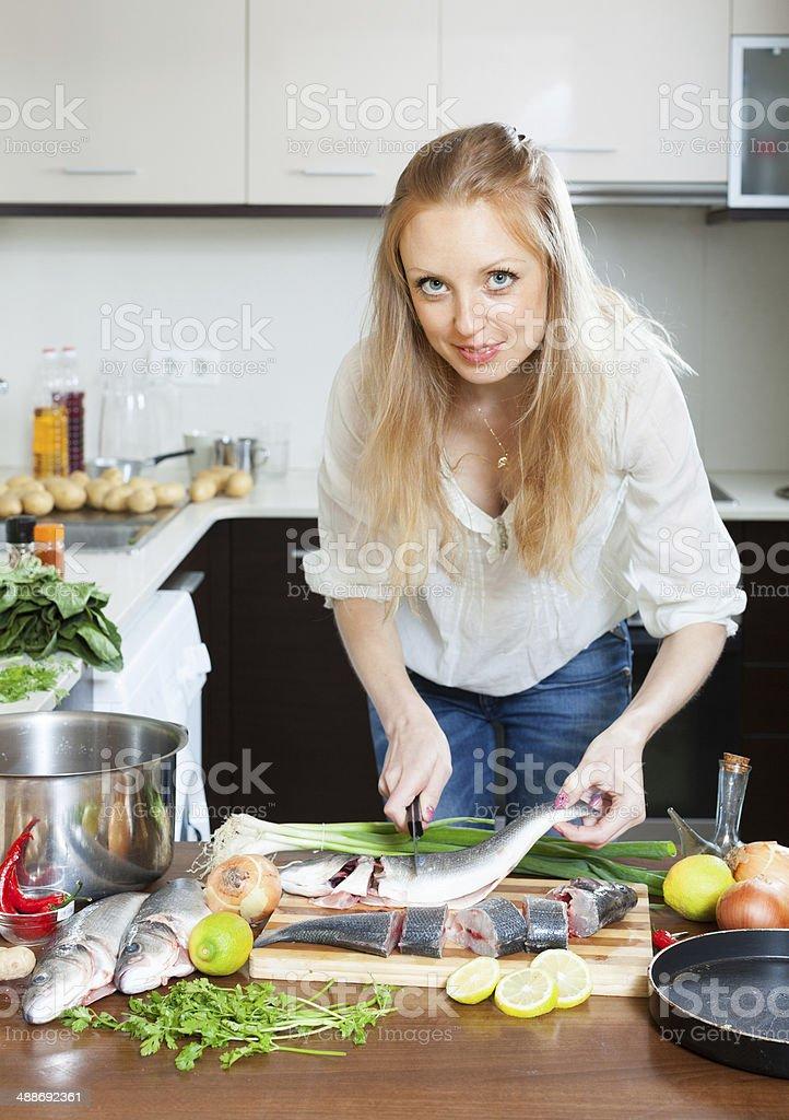 Blonde woman cutting raw fish stock photo