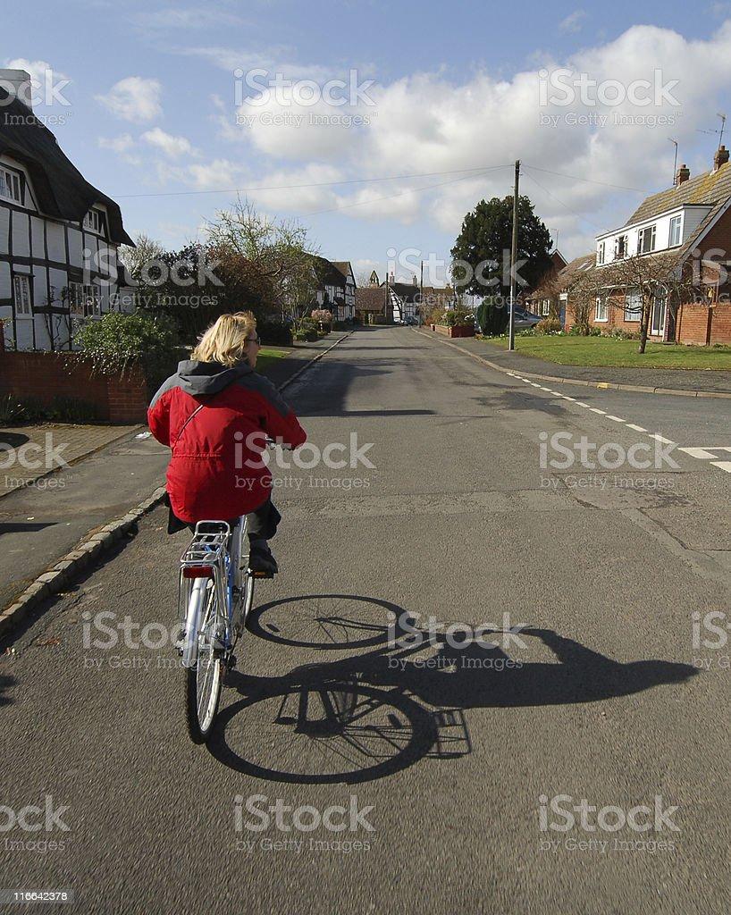Blonde woman cycling, village royalty-free stock photo