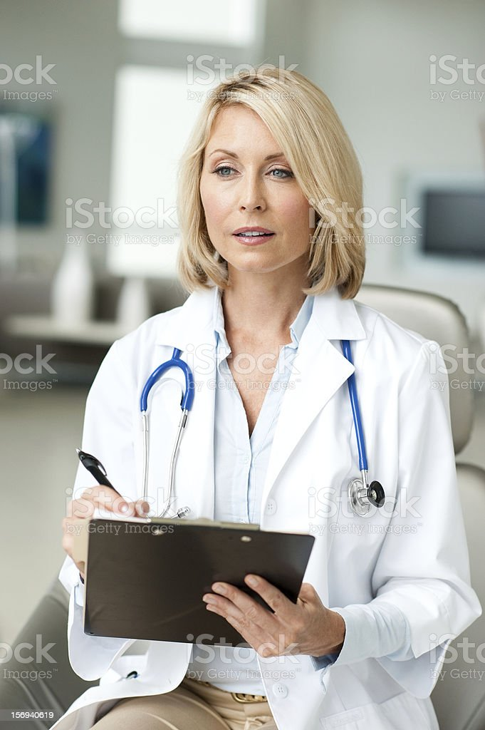Blonde Woman Doctor in Office with Clipboard royalty-free stock photo