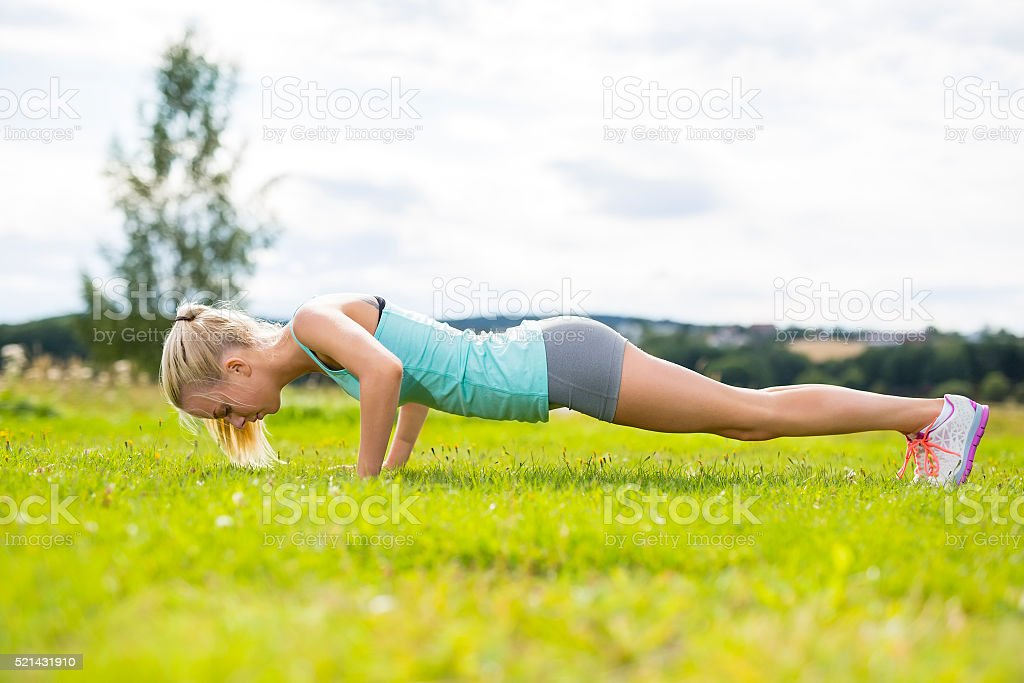Blonde woman doing push-ups outdoor in the park stock photo