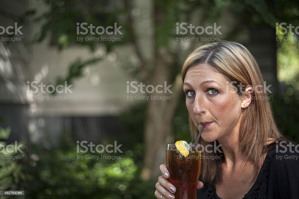 Blonde Woman Drinking Glass of Iced Tea royalty-free stock photo