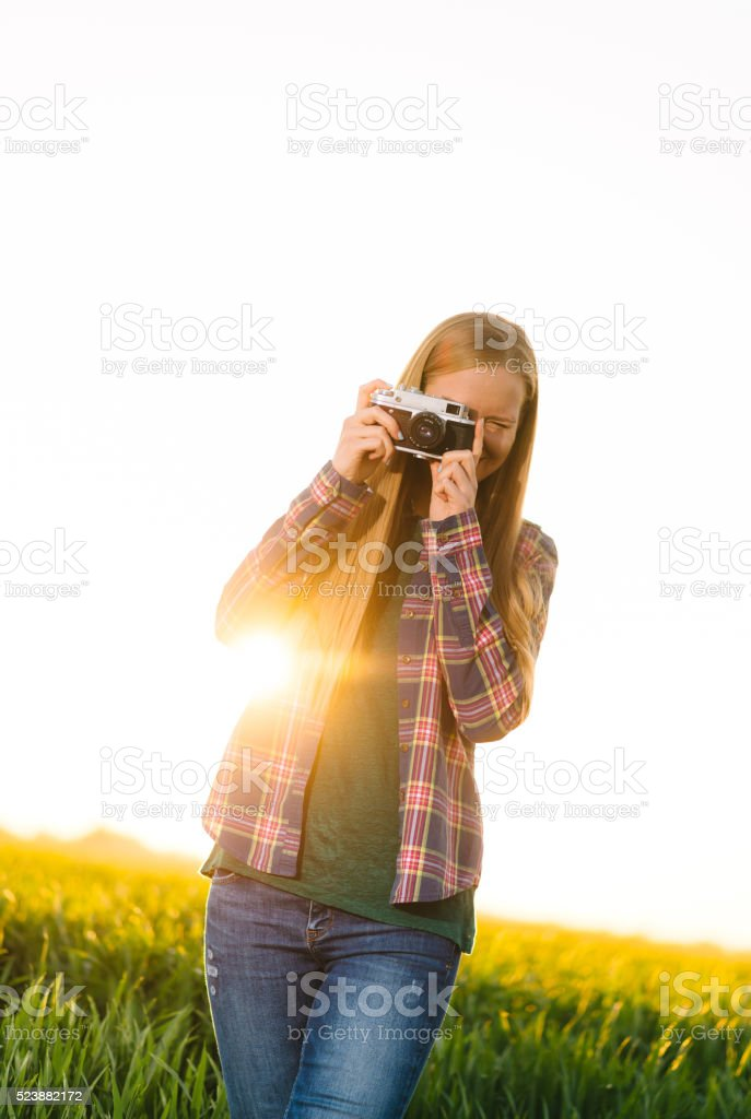 Blonde woman enjoys sun and summer and taking photos stock photo
