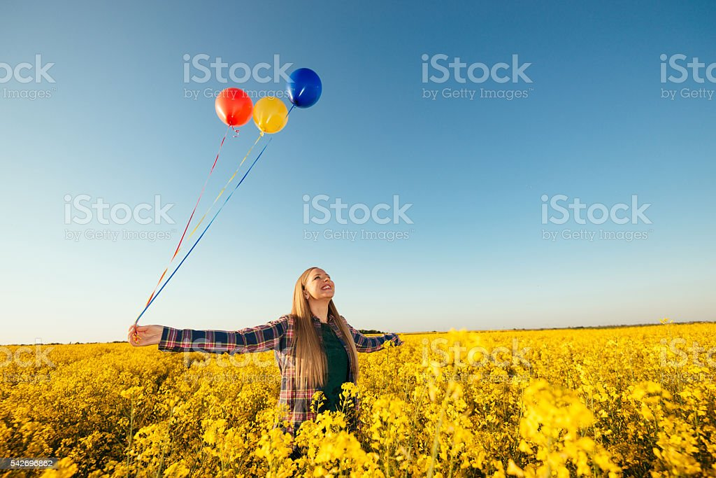Blonde woman enjoys sun and summer with balloons stock photo