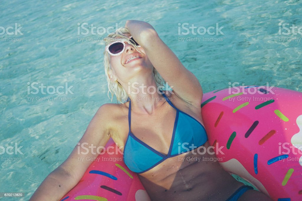 Blonde woman floating at the ocean, Maldives stock photo