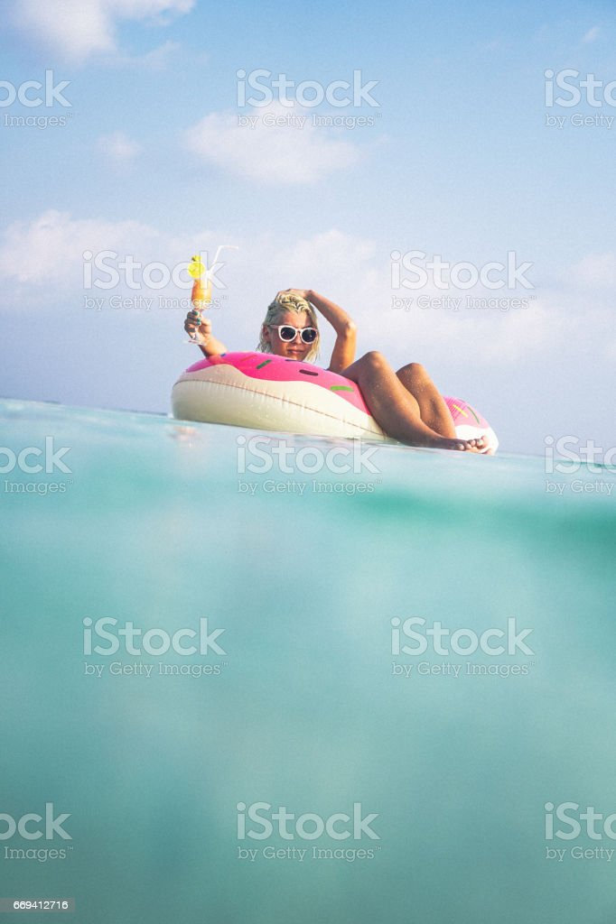 Blonde woman floating in the ocean, Maldives stock photo
