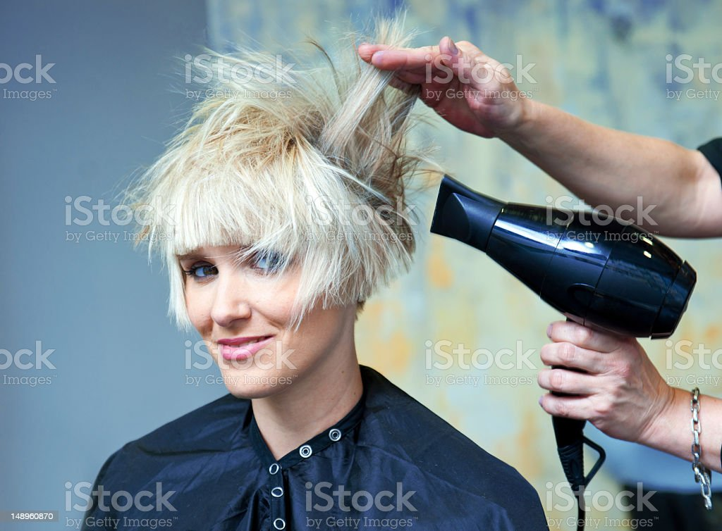A blonde woman getting her hair blow dried stock photo