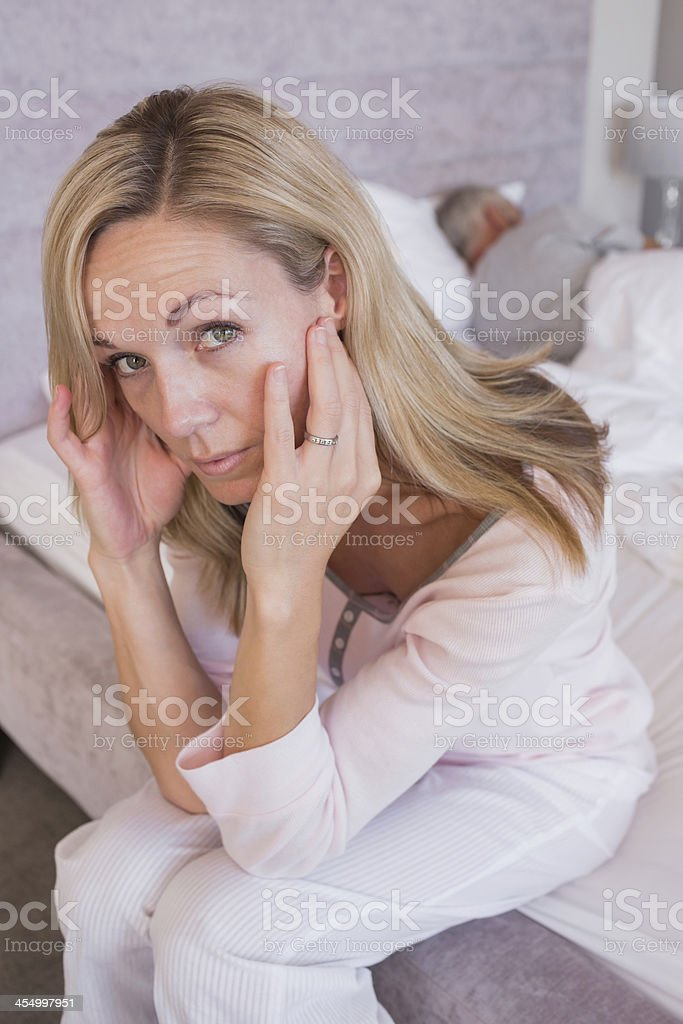Blonde woman has a headache while her husband is sleeping royalty-free stock photo