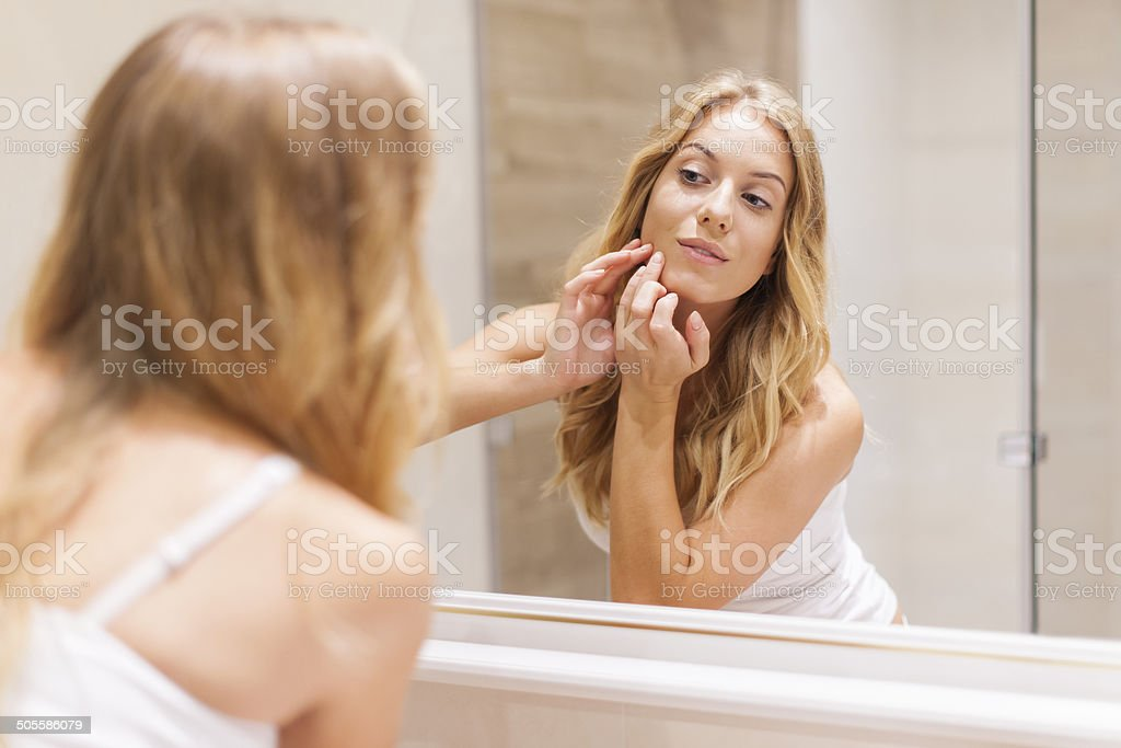 Blonde woman has problems with skin on the face stock photo