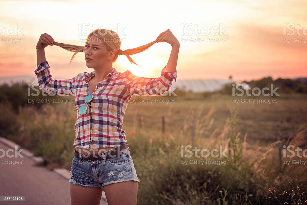 Blonde Woman having fun with her hair at sunset stock photo