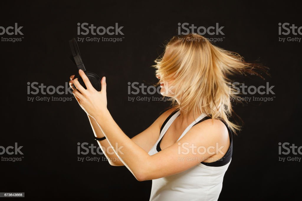 Blonde woman holding big headphones in studio stock photo