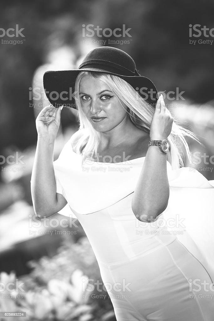 Blonde woman holding black hat stock photo