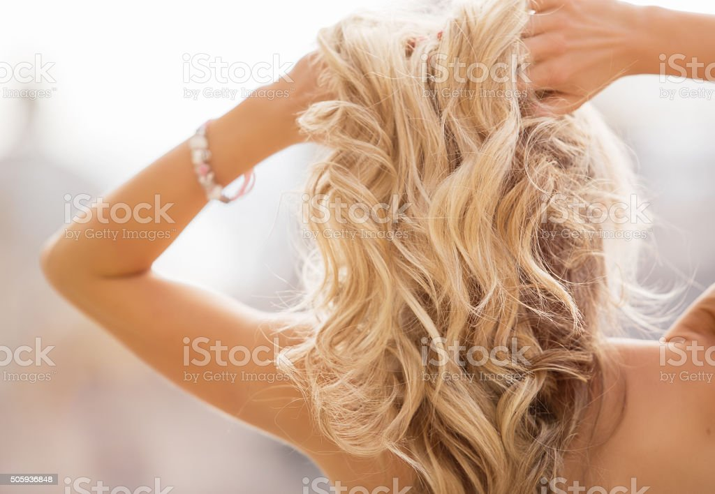 Blonde woman holding her hands in hair stock photo