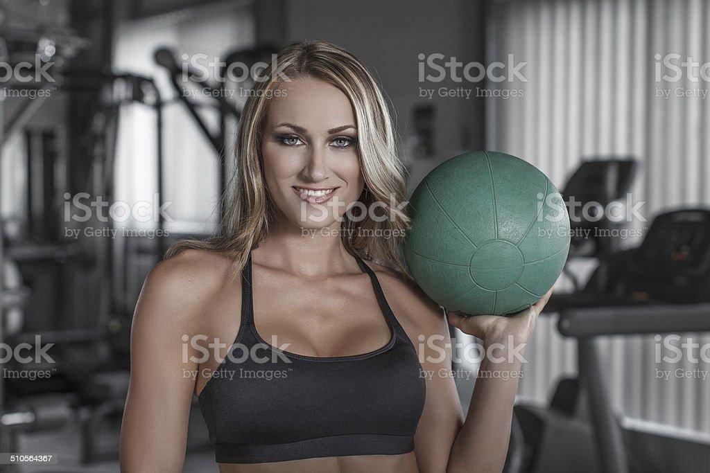 Blonde woman holding medicine ball royalty-free stock photo
