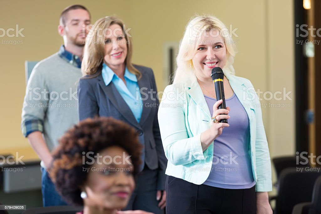 Blonde woman holding microphone asks question stock photo