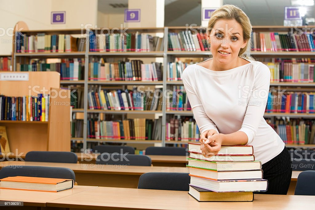 Blonde woman in a library with a stack of books stock photo