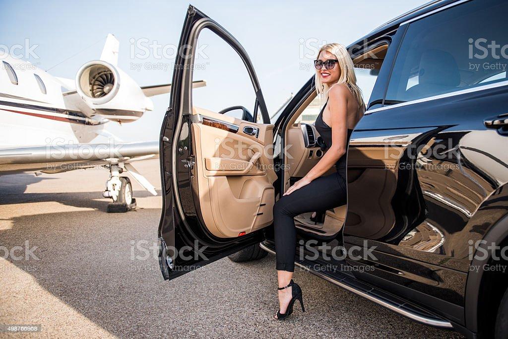 Blonde woman in black car stock photo