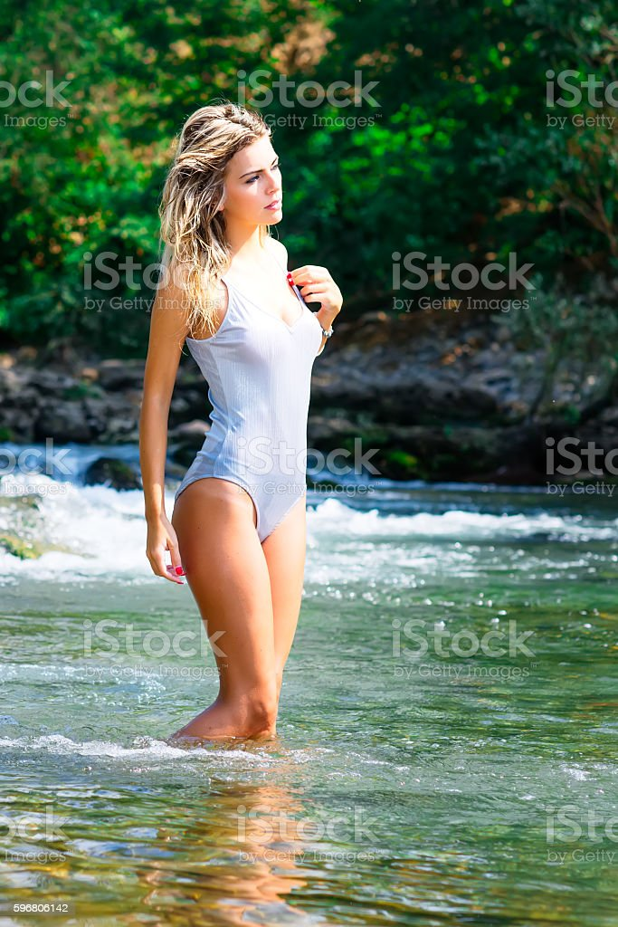 Blonde woman in body enters the river stock photo