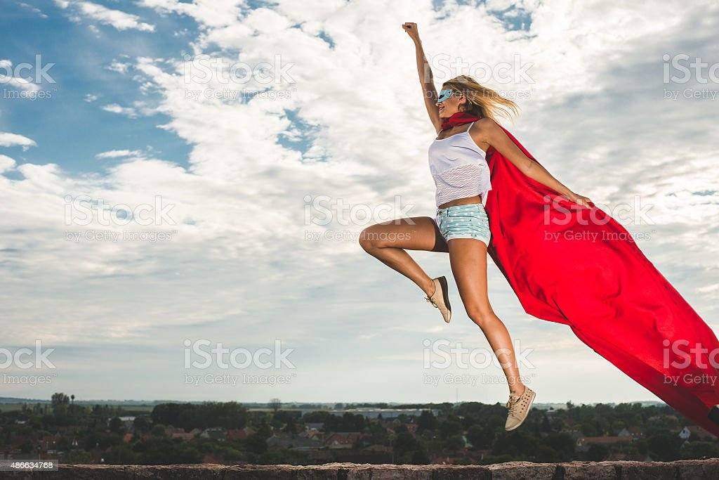 Blonde woman in red dress and red mantle jumping outdoor stock photo