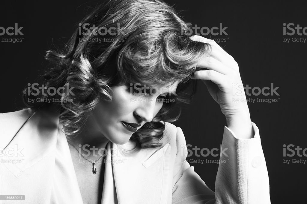 Blonde woman in white tux looking down, hand in hair. royalty-free stock photo