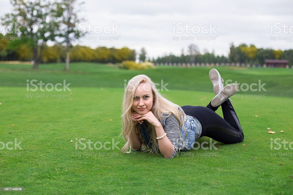 Blonde woman is lying on the golf field stock photo