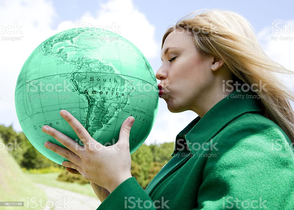 blonde woman kissing green globe royalty-free stock photo