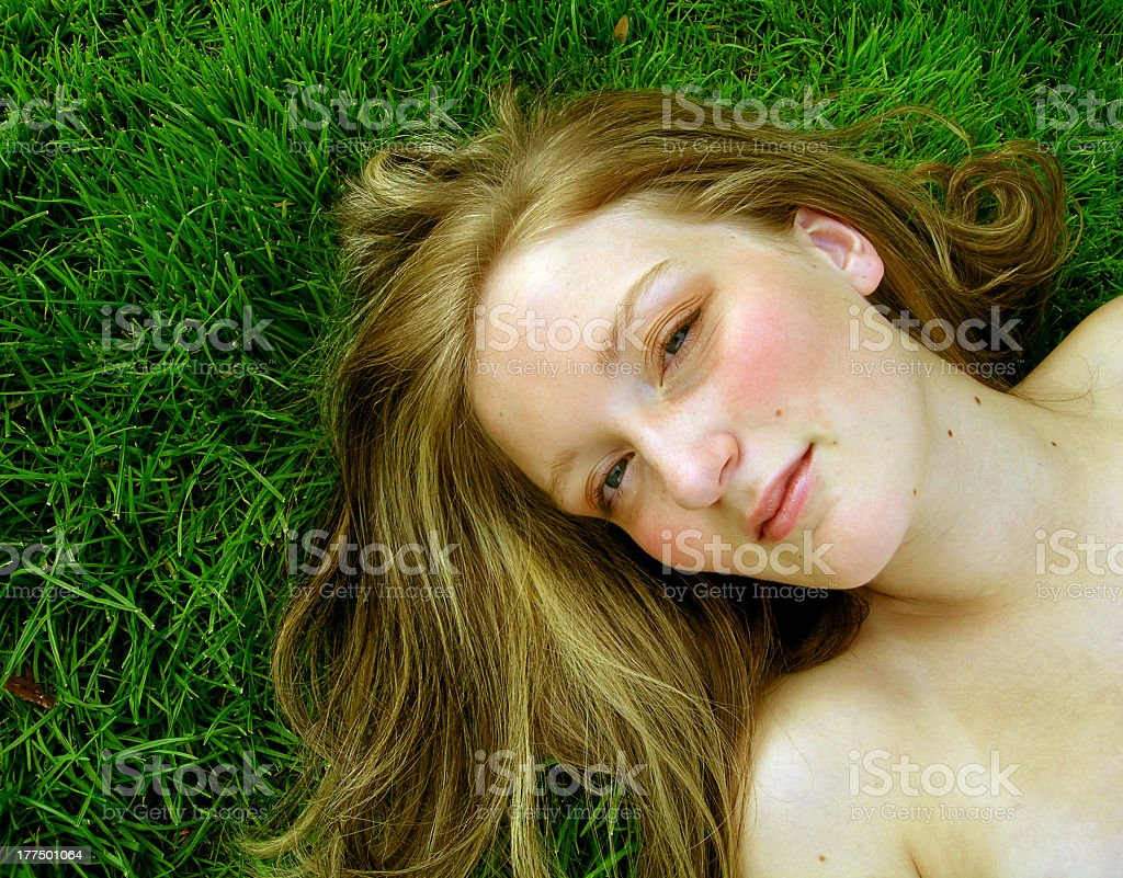 Blonde woman lying in grass looking up at camera stock photo