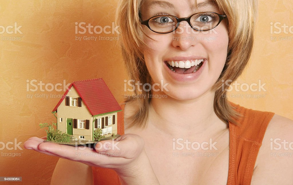 Blonde woman offering a house royalty-free stock photo