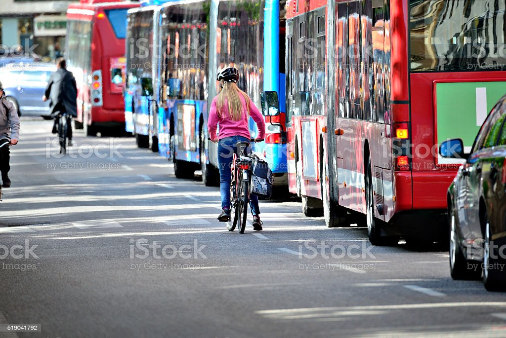 Blonde woman on bike and lane of buses stock photo