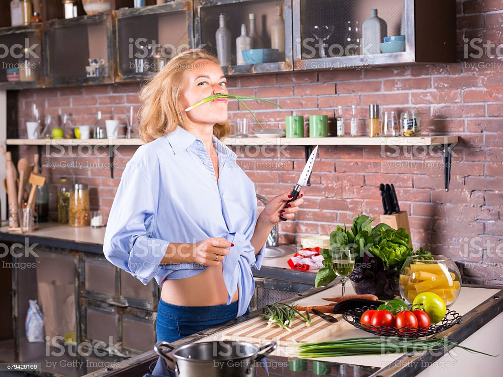 blonde woman on kitchen playing with green onion stock photo