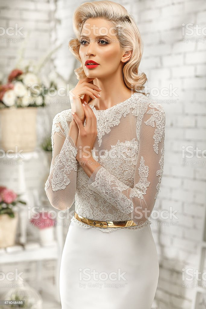 Blonde woman posing in a tight white dress with a gold belt stock photo