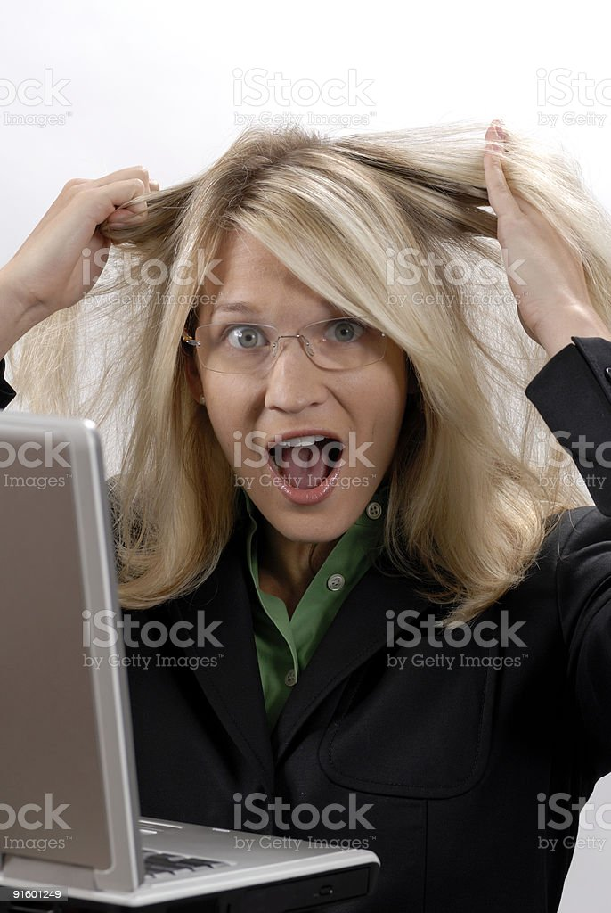 Blonde woman pulling her hair out over computer malfunction stock photo